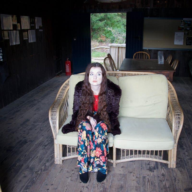Senhora branco-enfrentada triste em uma cadeira de vime imagem de stock royalty free