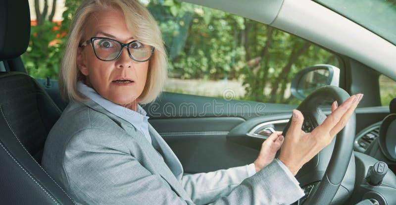 Senhora chocada e assustado ao conduzir um carro imagens de stock royalty free
