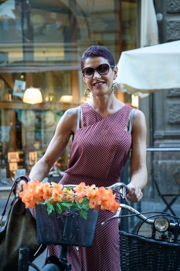 Senhora com ciclismo na cidade fotografia de stock royalty free
