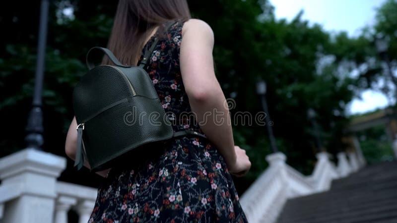 Senhora com o bagpack que está antes das escadas, superando o conceito das dificuldades da vida imagens de stock