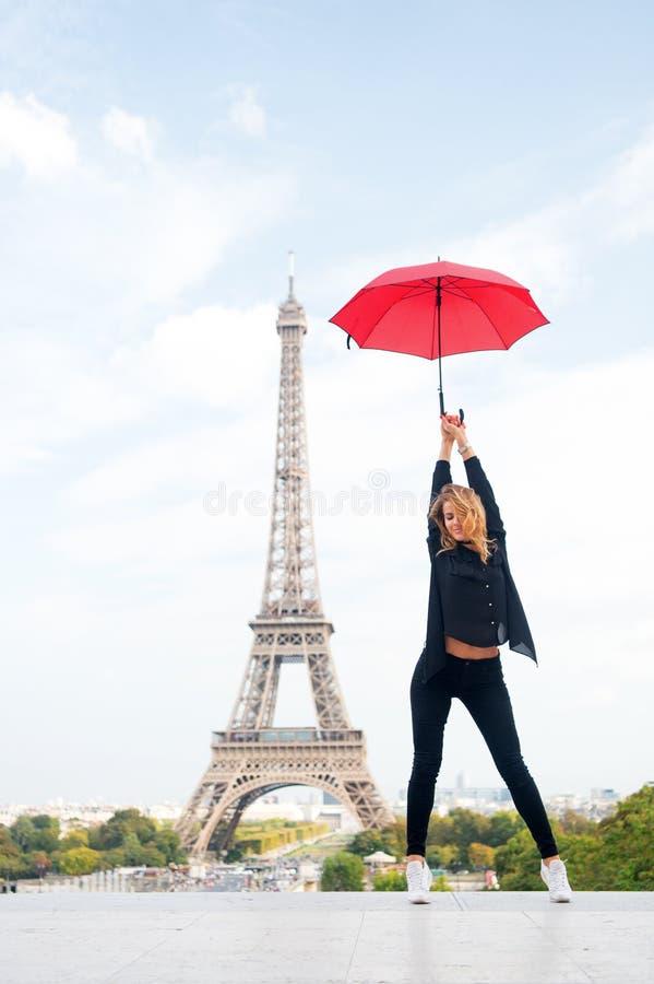 Senhora com o guarda-chuva que levanta na frente da torre Eiffel, fundo do céu O turista da senhora desportivo e o active andam n fotos de stock