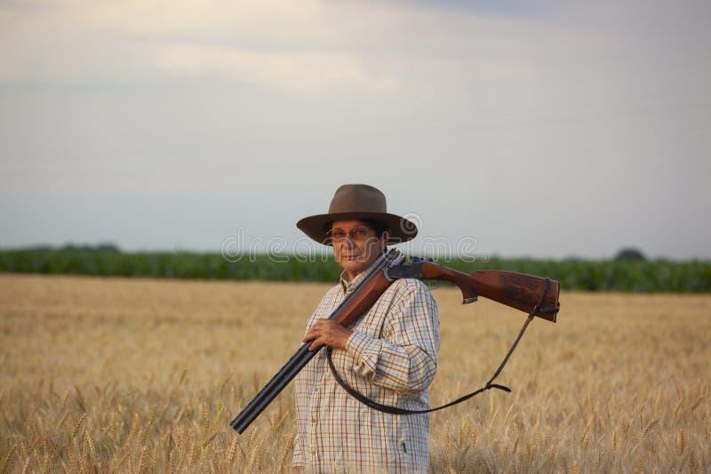 Senhora com o shootgun pronto para a caça no campo de grão imagem de stock
