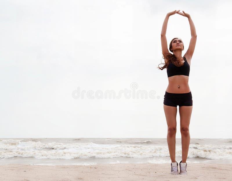 A senhora com sportwear está estando no lado direito do fundo é aumento suas mãos acima no ar e no corpo do aumento acima fotografia de stock