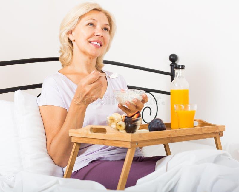 Senhora com suco de laranja, bagas e iogurte imagem de stock royalty free