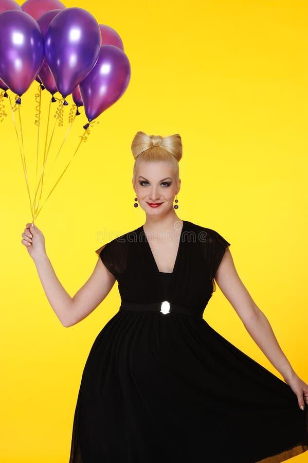 Senhora com um grupo de balões roxos fotografia de stock royalty free