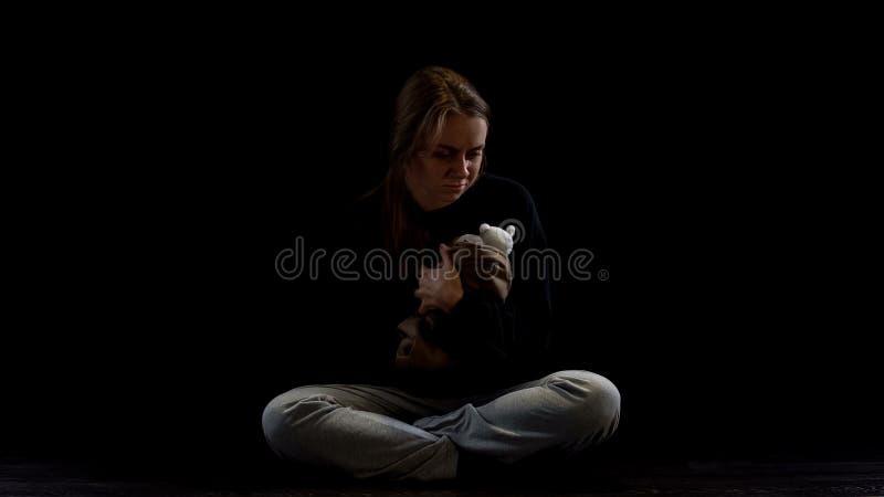 Senhora comprimida que senta-se na escurid?o que abra?a o urso de peluche, v?tima obst?trico da viol?ncia foto de stock