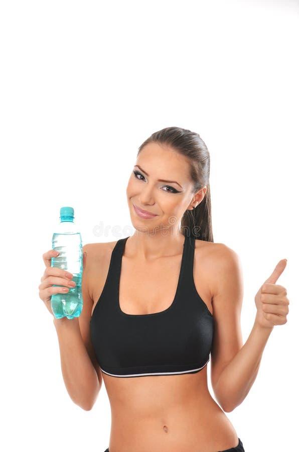 Senhora da aptidão que guarda uma garrafa da água e que dá os polegares acima imagens de stock royalty free
