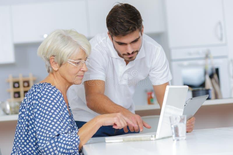 Senhora de ajuda do homem novo com computador imagens de stock