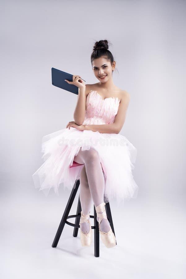 A senhora de beleza está usando um vestido de balé rosa e sapatos de balé, sentados em uma cadeira preta, segure o livro na mão foto de stock royalty free