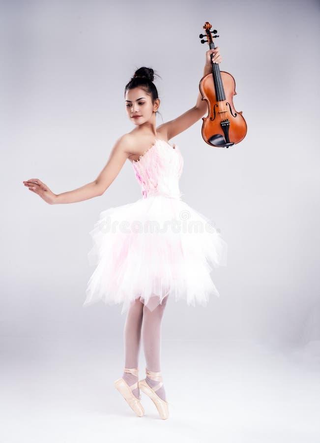 A senhora de beleza está vestindo terno de balé rosa, fica de pé com dedos, e dança com violino fotos de stock royalty free