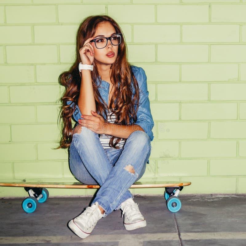 Senhora de cabelos compridos bonita com um skate de madeira perto de um verde fotografia de stock