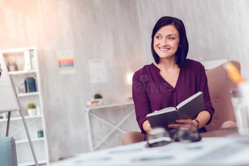 Senhora de cabelos curtos de fascínio de sorriso energética alegre que guarda um organizador pessoal fotografia de stock