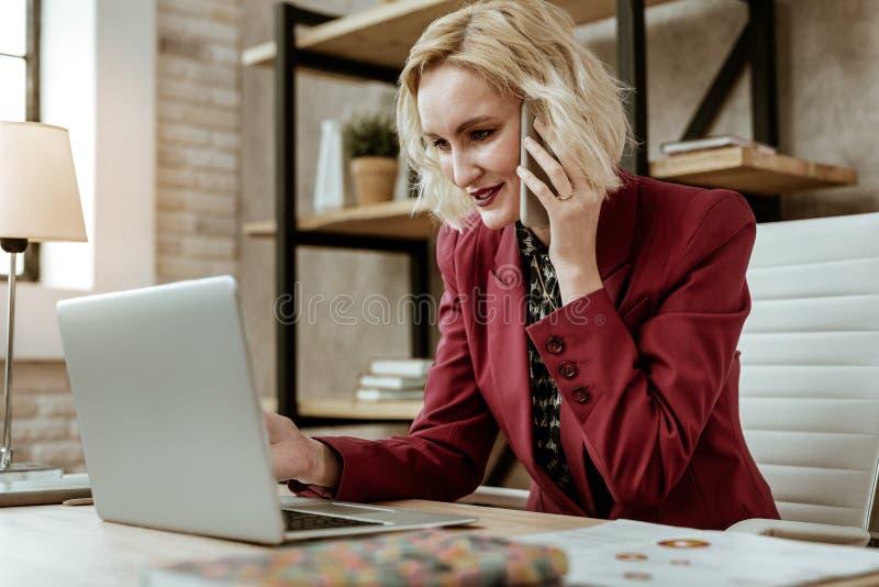 Senhora de cabelos curtos de sorriso no smartphone levando e na leitura do revestimento vermelho imagens de stock royalty free