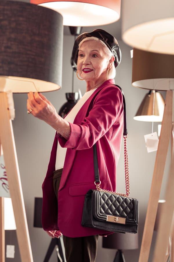 Senhora de envelhecimento brilhante à moda que seleciona a assoalho-lâmpada nova em iluminar a loja imagem de stock royalty free