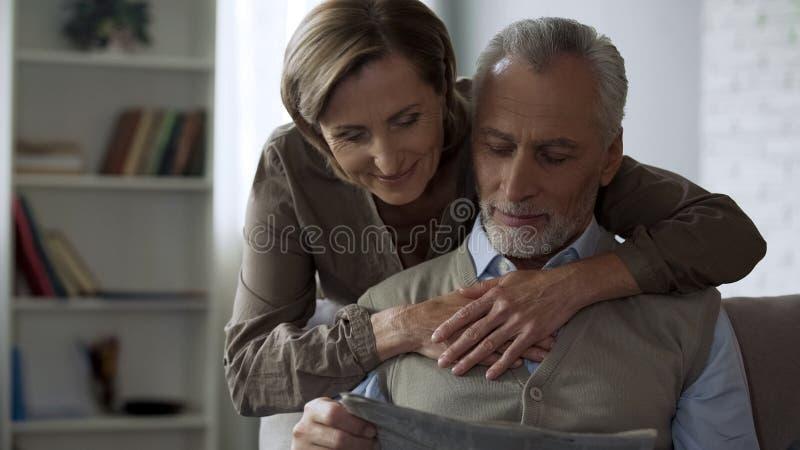 Senhora de envelhecimento que abraça seu marido, assento masculino no sofá e lendo o amor do jornal fotografia de stock
