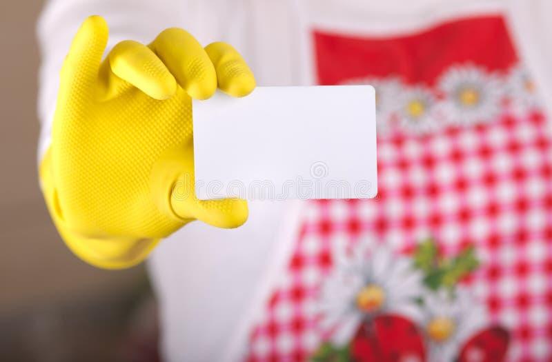 Senhora de limpeza que mostra o cartão fotografia de stock