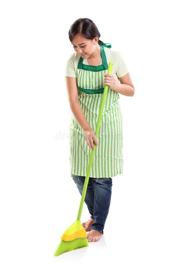 Senhora de limpeza que varre o assoalho, retrato do estúdio imagens de stock