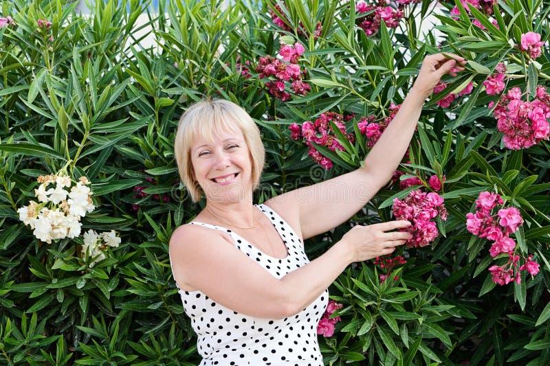 A senhora de meia idade caucasiano levanta e ri alegremente em flores de florescência fotos de stock royalty free