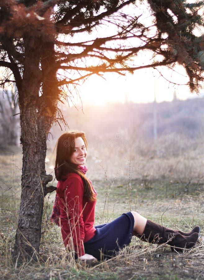Senhora de sorriso bonita que senta-se sob uma árvore com por do sol no fundo fotografia de stock