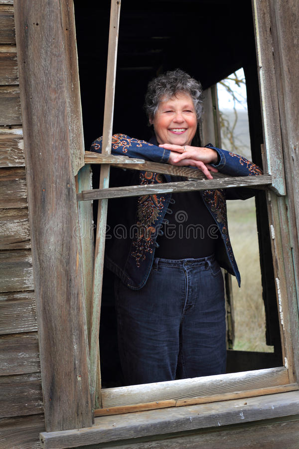 Senhora de sorriso na janela foto de stock royalty free