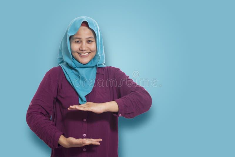 Senhora de sorriso nova que mostra algo grande entre suas mãos com imagem de stock