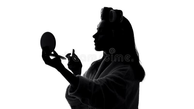 Senhora de sorriso que olha no espelho e em aplicar o batom, preparando-se para encontrar-se imagens de stock