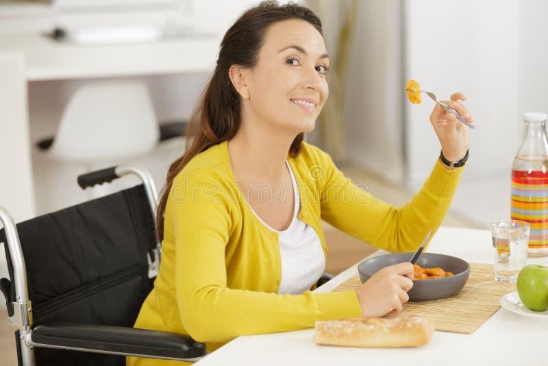 Senhora deficiente que come a refeição em casa imagem de stock royalty free