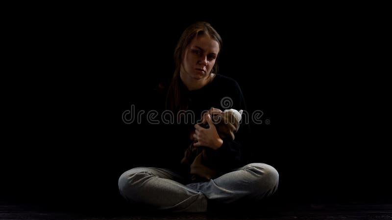 Senhora deprimida de grito que abraça o urso de peluche na escuridão, vítima obstétrico da violência fotografia de stock royalty free