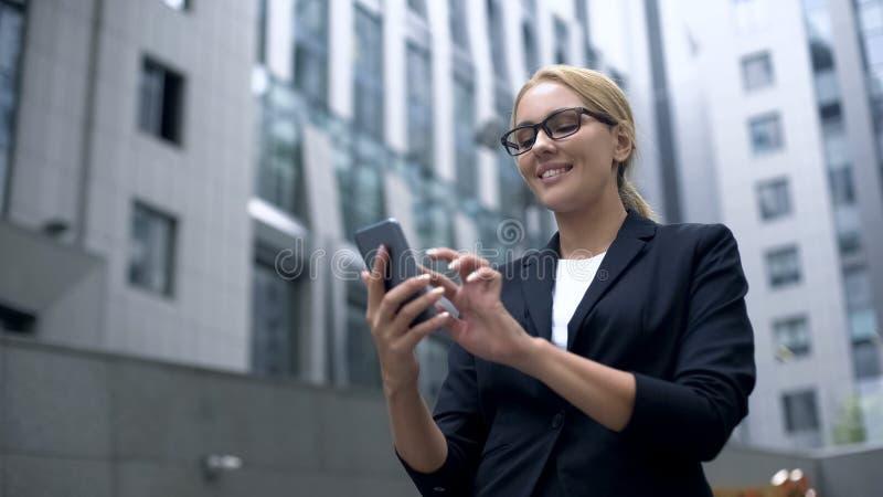 Senhora do escritório que texting com noivo e que sorri, conversando no app, datando o Web site foto de stock royalty free
