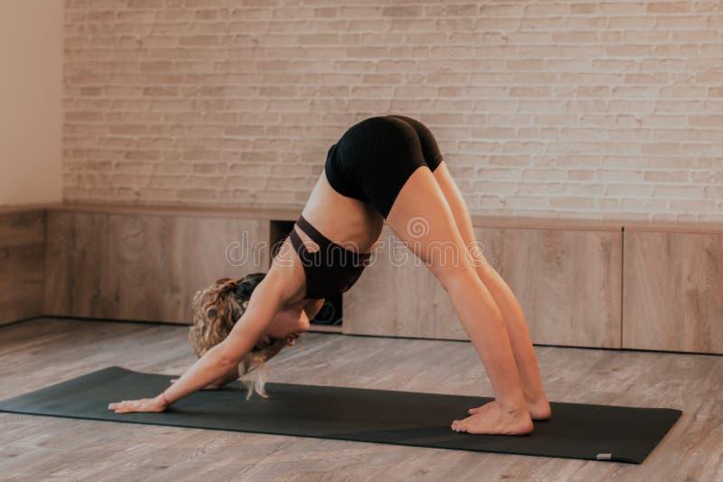 Senhora do estúdio da ioga que pratica uma meditação e que estica exercícios do corpo para todo o corpo é concentrada e de relaxa imagens de stock