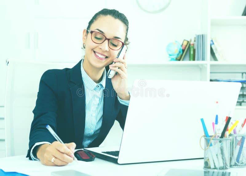 Senhora do negócio com telefone e o portátil espertos fotos de stock