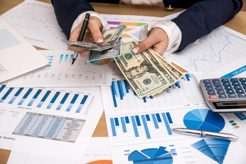A senhora do negócio conta dólares e verifica os gráficos foto de stock