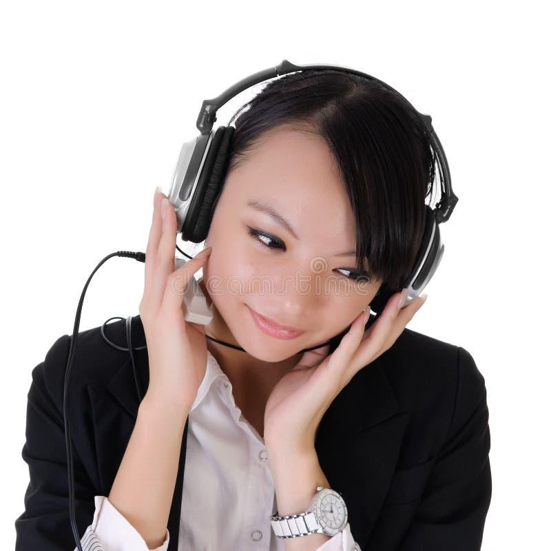 A senhora do negócio escuta música imagem de stock
