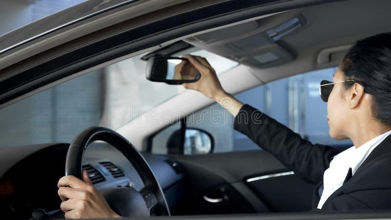 Senhora do negócio que olha no espelho retrovisor, conduzindo o automóvel, regras de tráfego fotografia de stock