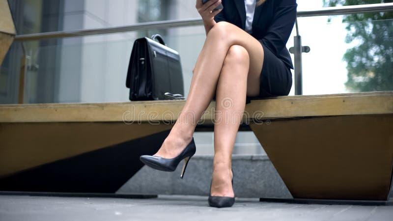 Senhora do negócio que senta-se no banco, escrevendo a mensagem ao sócio que tarde para encontrar-se foto de stock