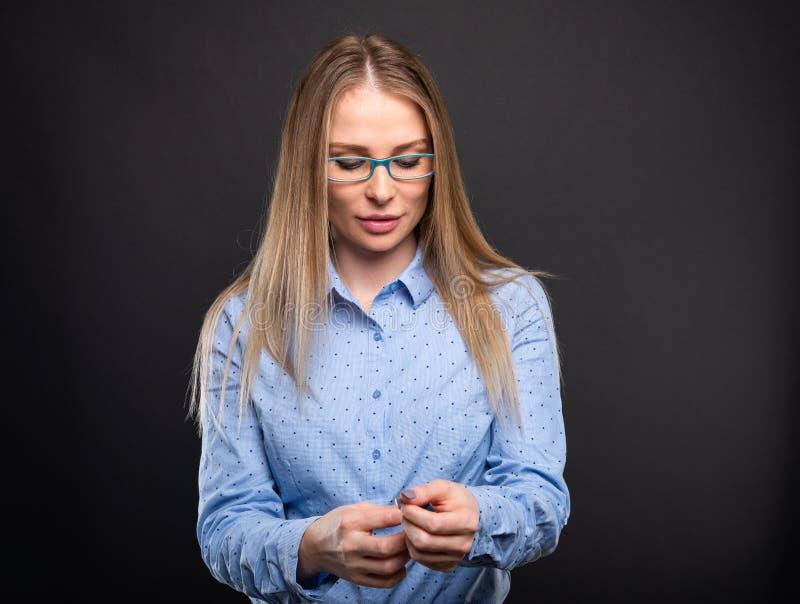 Senhora do negócio que veste os vidros azuis que arranjam sua luva imagem de stock royalty free