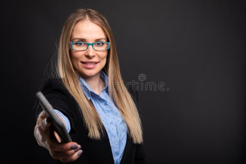 Senhora do negócio que veste os vidros azuis que entregam o smartphone imagem de stock royalty free