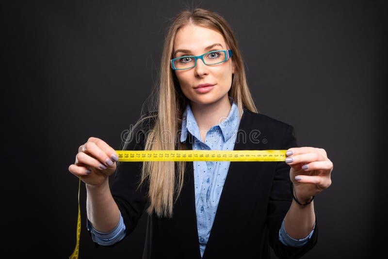 Senhora do negócio que veste os vidros azuis que guardam a fita de medição imagens de stock royalty free