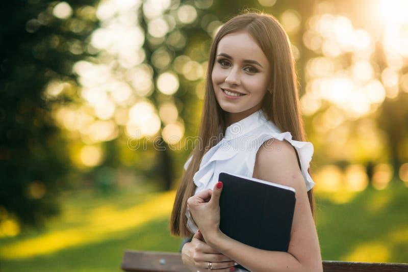 A senhora do negócio usa uma tabuleta no parque durante uma ruptura fotos de stock