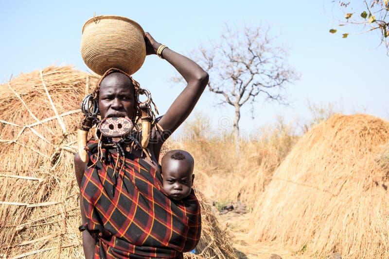 Senhora do tribo de Mursi que leva seu bebê fotos de stock