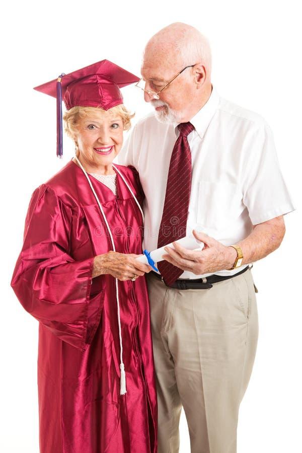A senhora e o esposo superiores comemoram sua graduação foto de stock