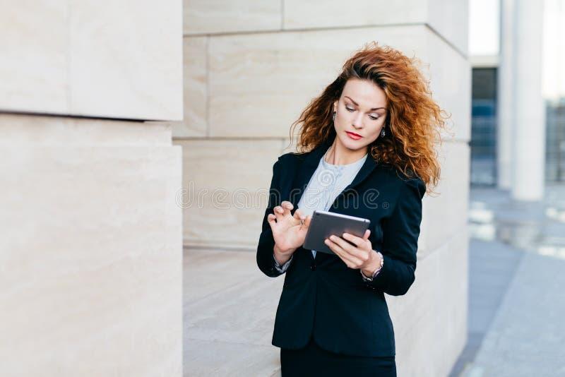 Senhora elegante com cabelo encaracolado, terno preto vestindo, mensagens de datilografia ou relatório comercial da fatura ao usa imagens de stock royalty free