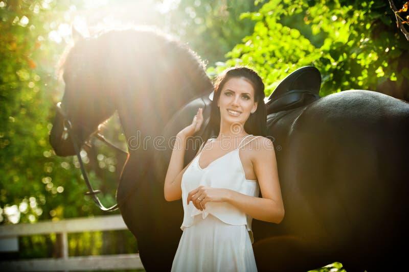Senhora elegante com o vestido nupcial branco perto do cavalo marrom na natureza Jovem mulher bonita em um vestido longo que leva fotografia de stock royalty free