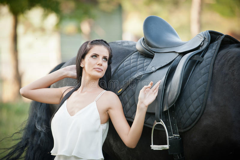 Senhora elegante com o vestido nupcial branco perto do cavalo marrom na natureza Jovem mulher bonita em um vestido longo que leva foto de stock