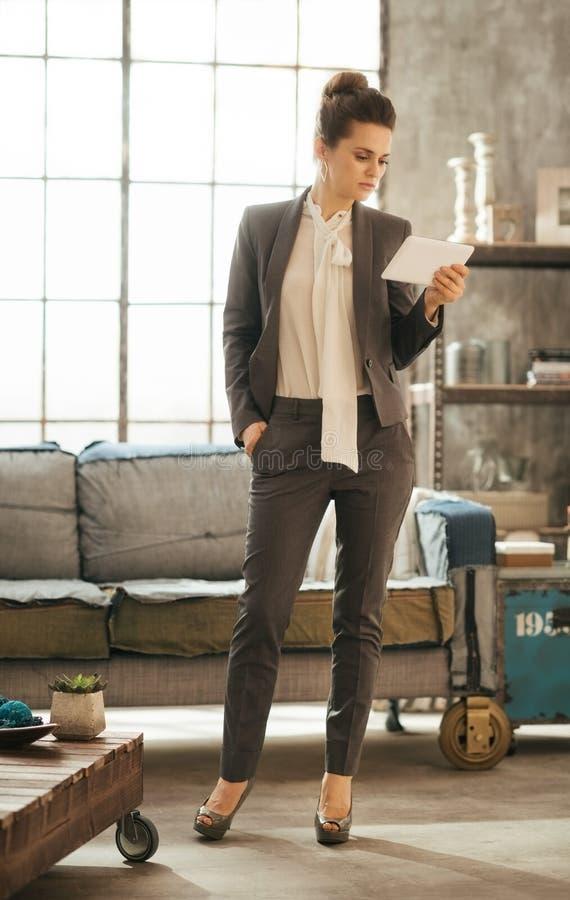 Senhora elegante do negócio que guarda a tabuleta do PC no apartamento do sótão imagens de stock