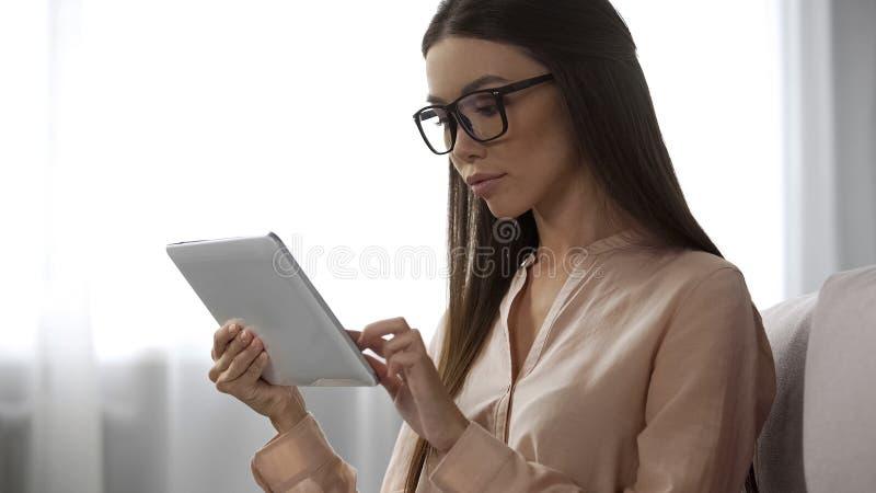 Senhora elegante nos vidros que analisa as letras do e-mail, verificando o dobrador do inbox na tabuleta imagem de stock
