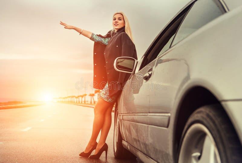 Senhora em sapatas do salto alto com o carro broked na estrada imagem de stock