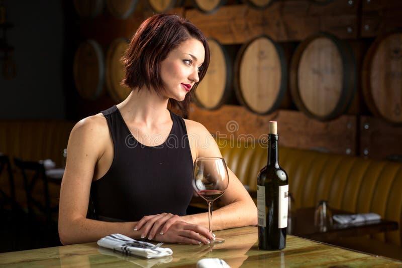 Senhora em um restaurante luxuoso caro com uma garrafa de elegante elegante do vinho foto de stock royalty free
