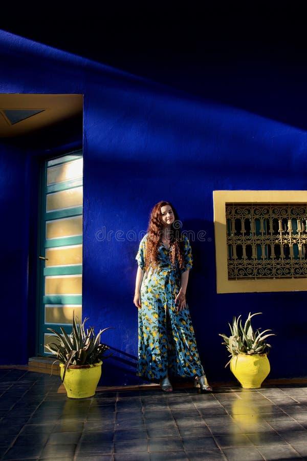 Senhora em um vestido azul e amarelo em um terraço de harmonização imagens de stock royalty free