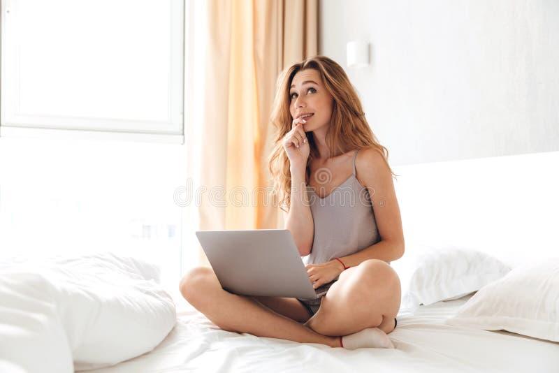 Senhora emocional feliz que senta-se na cama que conversa dentro pelo portátil imagens de stock royalty free